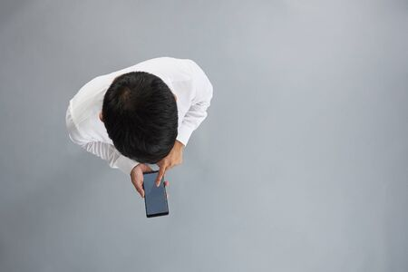 One man using smartphone isolated on gray background above top view Archivio Fotografico