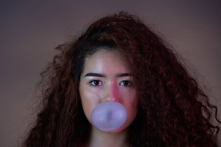 Close-up portrait of girl with bubble gum ball on colorful background Banque d'images