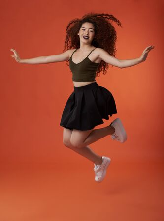 Jumping happy young brunette woman with curly hair