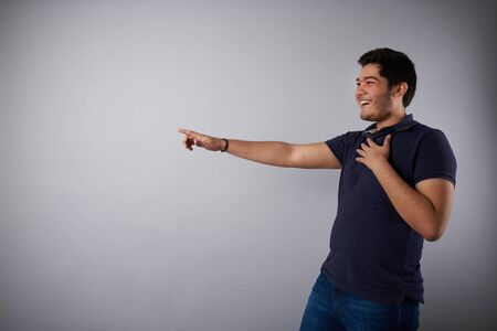 Laughing young man and point finger on side in studio background Stock fotó