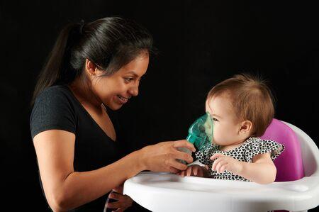 Happy baby girl using inhalation mask isolated on black background Reklamní fotografie