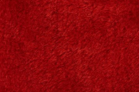 Red fluffy fabric background. Texture of pink fur