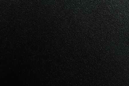 Dark matte metal background macro close up view. Black texture with granule