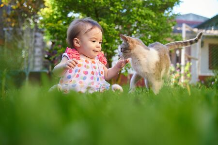 Baby girl interacting with cat on natural park background