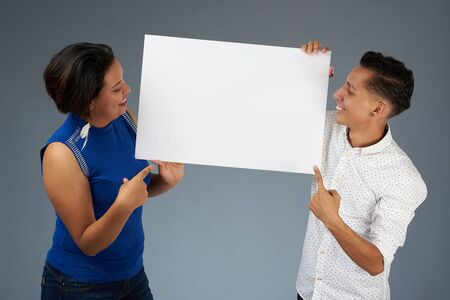 Young people point at copy space on banner isolated on gray studio background
