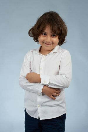Portrait of smiling kid with crossed arms isolated on gray studio background