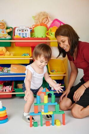 Babyactiviteit in kasteel bouwen. Verpleegkundige speelt met kind in de kinderopvang Stockfoto