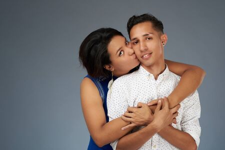 Pretty young couple kissing on gray studio background