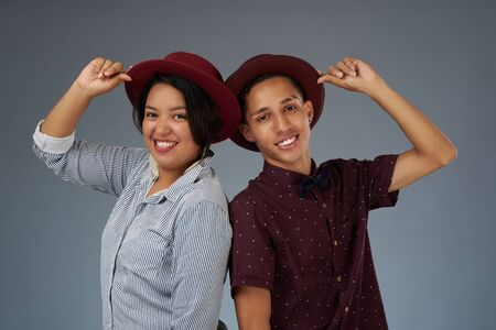Portrait of young hipsters in red hats isolated on gray studio background Stock Photo