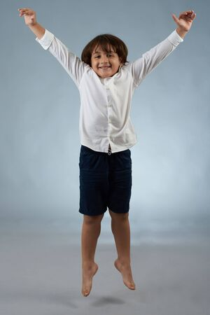 Happy smiling jumping little kid isolated on gray studio background