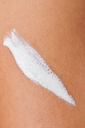 Applying white skin cream for sun protection close up view