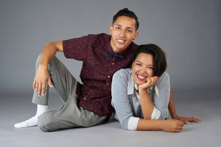 Cheerful young hipster couple on gray studio background