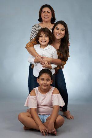Portrait of happy hispanic grandma and kids on gray studio background Stock Photo