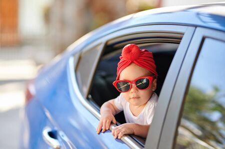 Small baby girl in fashion red sunglasses looking out from car window Banco de Imagens