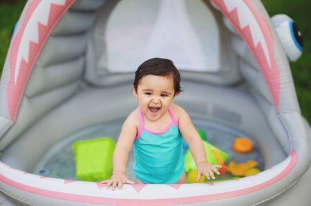 Baby girl screaming in pool on home garden