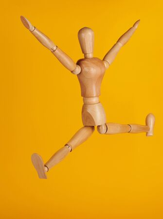 Wooden man in jumping pose isolated on yellow background