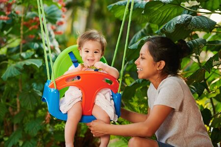 Mom with daughter play with swings on garden background Фото со стока