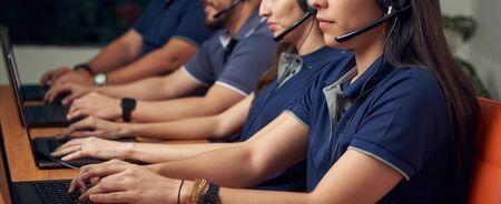 Bureau de l'équipe d'assistance téléphonique travaillant avec des ordinateurs portables et des écouteurs