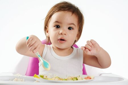 Cute baby eating healthy food on high chair isolated