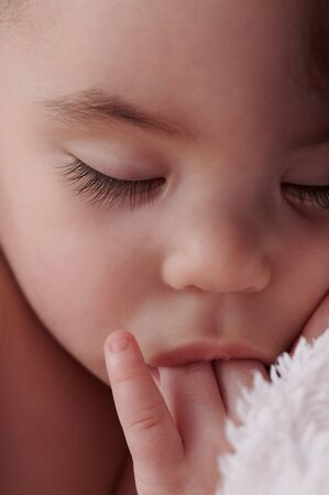 Newborn with fingers in mouth close up