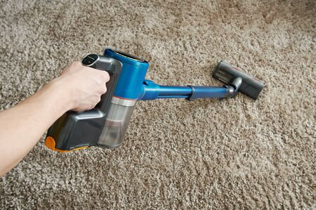 Cleaning carpet with vacuum cleaner on gray background