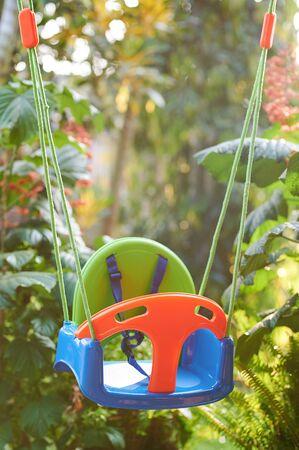 Empty kid swings on blurred green sunny background Stockfoto