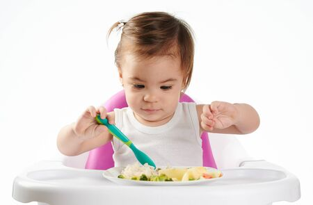 Baby girl trying new food isolated on white studio background
