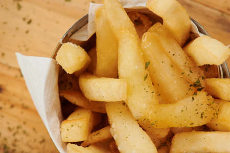 Crispy french fries in cup on wooden table close up view