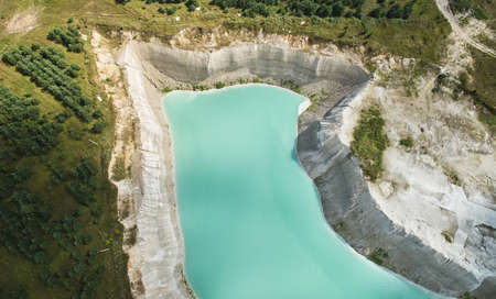 Green water in quarry aerial above top view on bright sunny day Archivio Fotografico