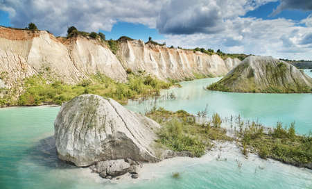 Quarry with green water and rocks aerial above drone view