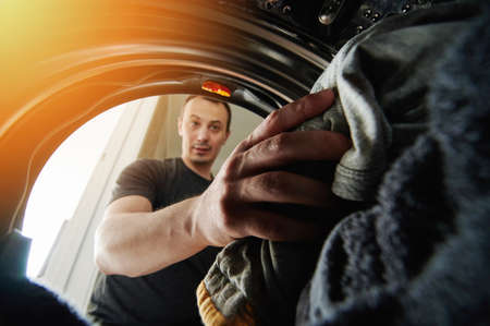 Man loading dirty cloth inside washing machine view from inside