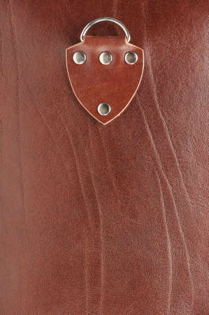 Leather patch with metal buttons on brown skin backgrond
