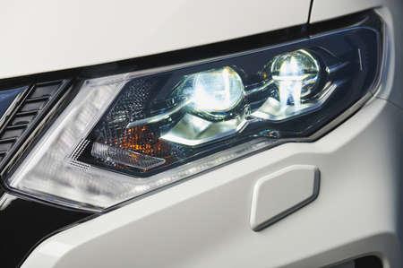 Headlamp in white car close up view. Vehicle headlight real photo. Polish car light service