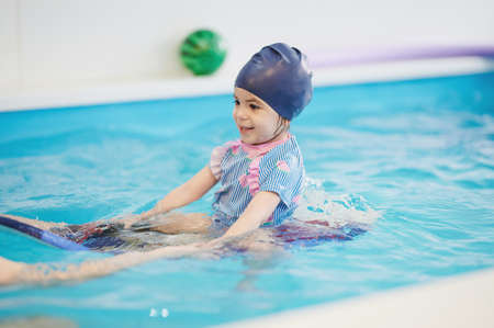 Child practice ride on board in swimming pool water. Kids swimming classes theme