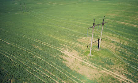 High voltage electric line towers on green meadow background aerial above top view