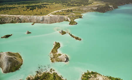 Green in big quarry water aerial drone view on bright sunny day Standard-Bild