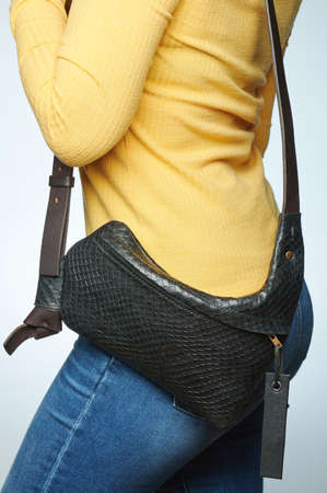 Small black leather bag on woman waist isolated close up view Standard-Bild