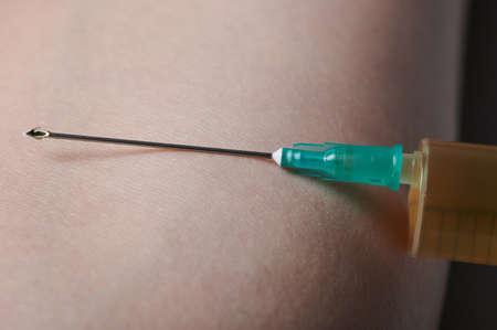 Dose of vaccine in syringe on human skin background macro view Standard-Bild