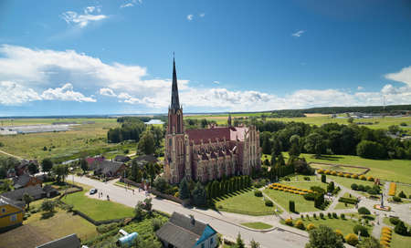 Red catholic church on blue sky background aerial view