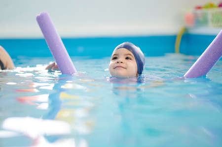 Happy floating child in pool blue water blurred background