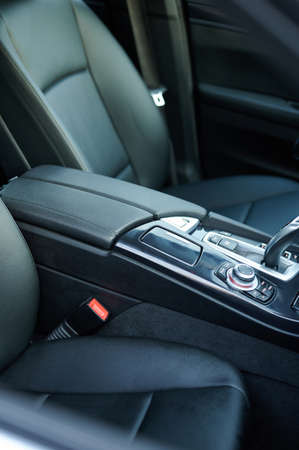 Leather black armrest in car console with gear stick close up view Standard-Bild