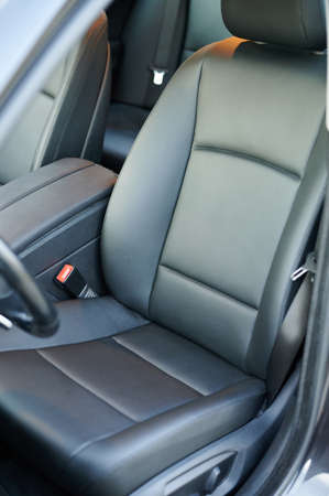 Clean dark black leather driver car seat with handrest