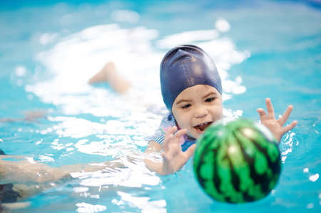 Kid catching ball in blue water pool. Swimming exercise at school