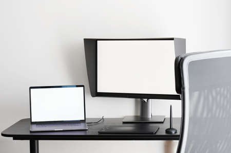 Table with laptop and pc monitor on white wall background