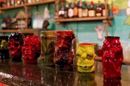tiki glasses stand on the bar of the restaurant