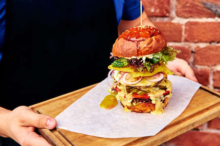 tall, big burger on a tray in hands