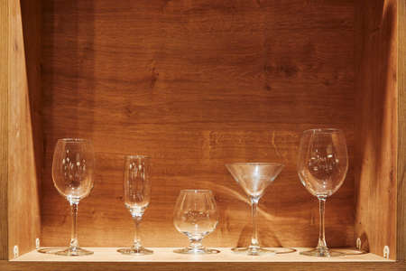 Different types of empty glasses on a wooden background