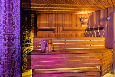 Minsk, Belarus, 03.03.2019: Interior of wooden finnish sauna with birch broom, bucket and stove. The Finnish sauna is a substantial