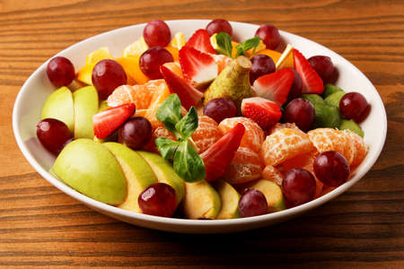 berries and fruits, mandarins, grapes, apple, pear, strawberries and cherries in a white plate, stand on a wood table