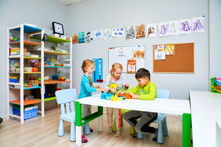 Russia, Moscow, 01.01.2019, two girls and a boy in kindergarten are sitting at a table and playing toys